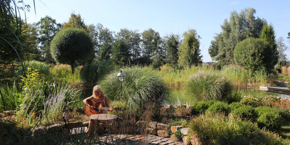 Frau mit Gitarre im Garten
