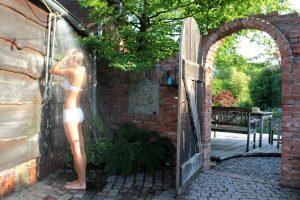 Frau unter Outdoordusche